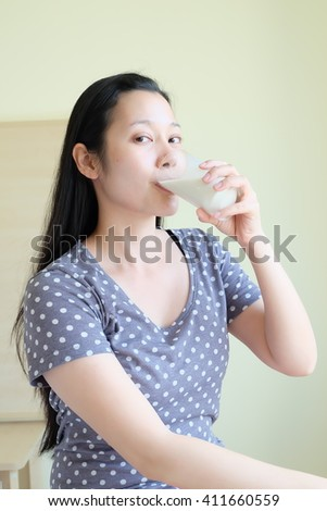 healthy asian woman is drinking milk from a glass - stock photo