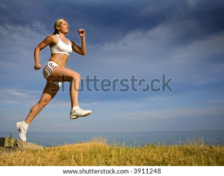 healthy athlete running on the beach in the summer - stock photo