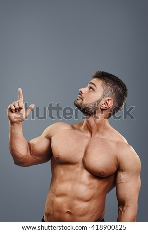 healthy athletic young man with muscles pointing finger up isolated on grey background. Vertical portrait of strong bodybuilder with perfect torso pointing to copyspace above head - stock photo