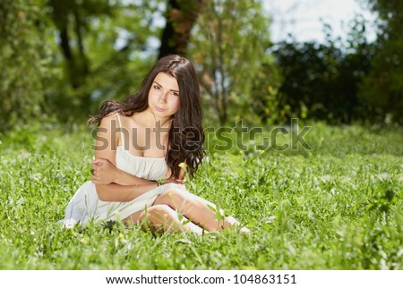 Healthy attractive young white girl posing outdoors in a bright sunny summer day