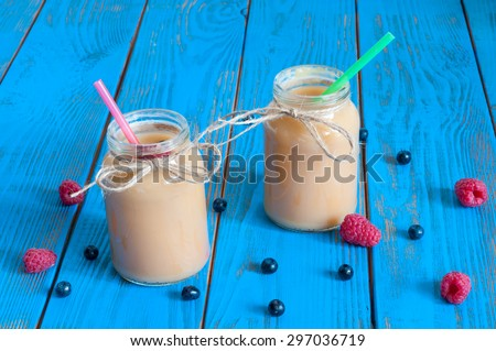 Healthy baby food: apple banana or apricot puree in mason jar, fresh raspberry. Light rural wooden background. Unique perspective, selective focus. - stock photo