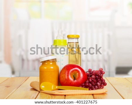 Healthy baby food: milk, juice, puree, and fresh fruit on the background of the kitchen.