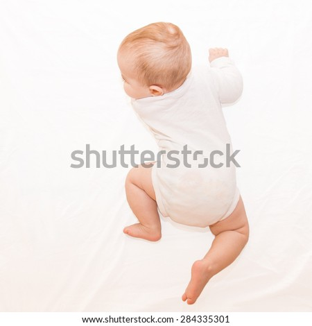 Healthy baby in white body lying on his tummy, learning and trying to crawl on light sheet background. Upper view. - stock photo