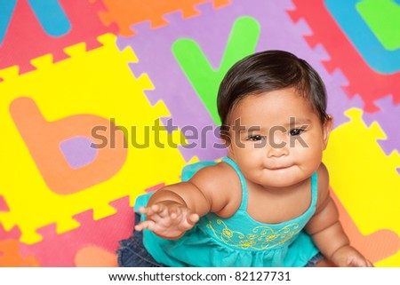 Healthy baby sitting in a colorful play mat - stock photo