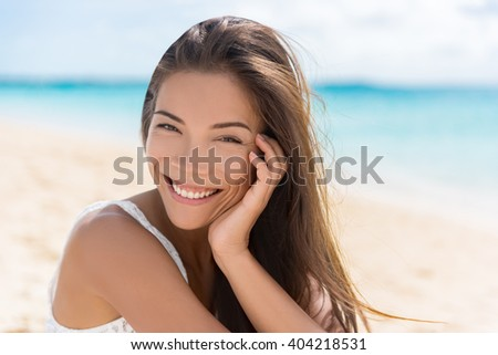Healthy beautiful Asian multiracial woman on beach. Portrait of pretty Chinese Caucasian mixed race brunette girl in her 20s relaxing on summer vacations. Confident and modern young adult. - stock photo