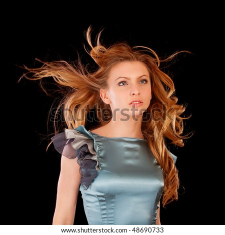 Healthy beautiful long hair in motion created by wind, isolated on black background.