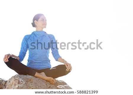 Healthy beautiful woman sitting on a rock in a yoga position against a sunny sky with flare, relaxing contemplating outdoors. Sport and fitness activities, healthy recreation, aspirational lifestyle.