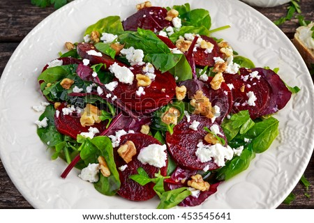 Healthy Beet Salad with fresh sweet baby spinach, kale lettuce, nuts, feta cheese and toast  melted  - stock photo