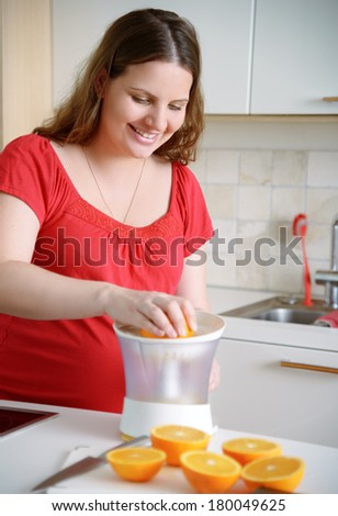 Healthy beginning: young pregnant woman cutting oranges to make orange juice at home kitchen and smiling.