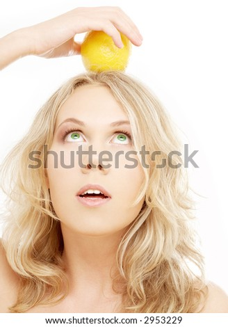 healthy blond holding lemon on her head over white