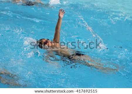 healthy boy back stroke swims in swimming pool , Asian young kid training with swim goggles  - stock photo