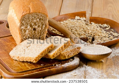 Healthy Bread and flour on a  wooden background. Selective focus - stock photo