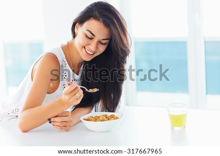 Healthy breakfast. Attractive young woman smiling and enjoying morning with a spoon in her hand and a bowl of cereal looking down and smiling.  - stock photo