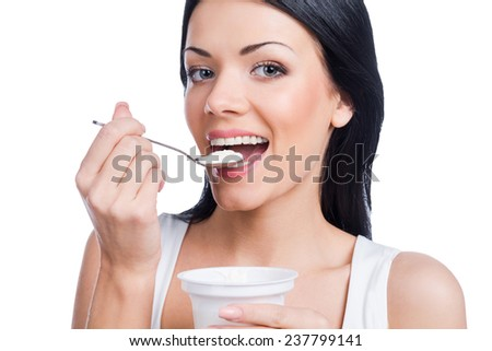 Healthy breakfast. Beautiful young smiling woman holding a spoon with sour cream while standing against white background - stock photo