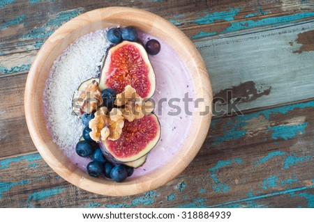 Healthy breakfast berry smoothie bowl of blueberry and strawberry blended with kefir yogurt and topped with fresh fig,blueberries,walnuts and coconut. Served in a wooden bowl on a rustic wooden table. - stock photo
