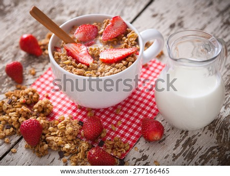 Healthy breakfast. Bowl of milk with granola and strawberries. - stock photo