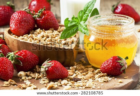 Healthy breakfast buffet with homemade muesli, honey, strawberries and milk, selective focus - stock photo