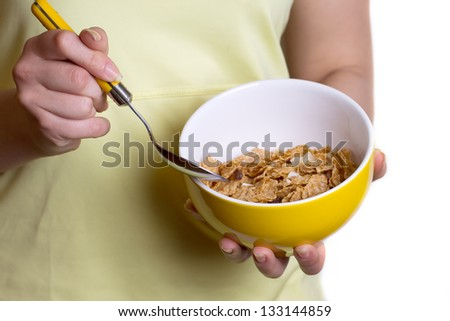 Healthy breakfast - cereal in the yellow bowl in female hands
