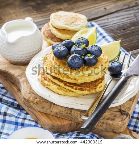Healthy breakfast classic. Several domestic hot pancakes with fresh ripe blueberry lime zest, honey on a white plate in the batch submission to breakfast on a wooden dark background. selective focus - stock photo