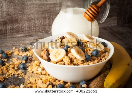 Healthy breakfast concept with oat flakes and fresh berries on rustic background. Food made of granola and musli. Healthy banana smoothie with blackberries, honey and milk. - stock photo