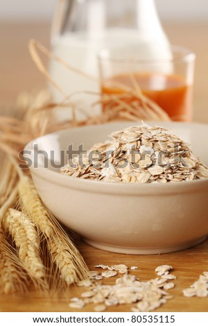 Healthy breakfast consisting of oatmeal, milk and carrot juice - stock photo