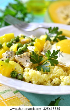 Healthy breakfast - couscous,vegetable ragout with chicken and fried egg on a table.