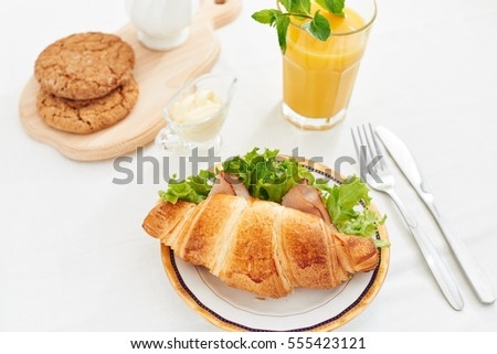 Healthy breakfast croissant sandwich with ham fresh salad orange juice with mint on white background