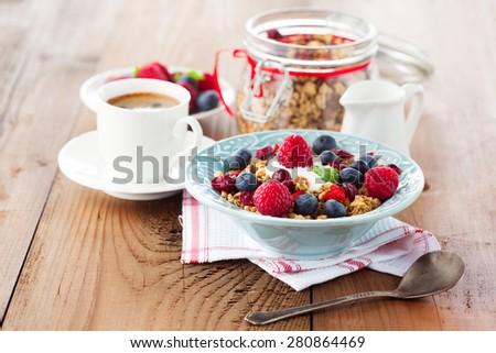 Healthy breakfast - cup of coffee, muesli and fresh berries on rustic wooden background, selective focus, health and diet concept - stock photo