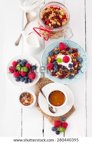 Healthy breakfast - cup of coffee, muesli and fresh berries on white wooden background, top view, health and diet concept - stock photo