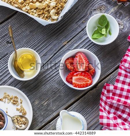 Healthy breakfast dessert. Crunchy granola with homemade pecan nuts served with fresh strawberries, milk, yogurt, liquid honey and fresh oregano. On a dark wooden background - stock photo