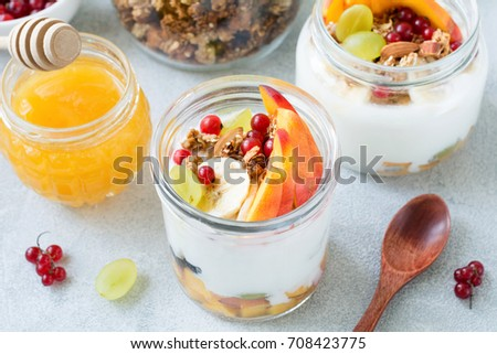 Healthy breakfast food table: granola, fruits, yogurt and honey. High angle view