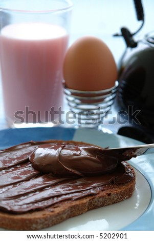 Healthy breakfast for kids with milk, eggs and hazelnut choco on their bread - stock photo