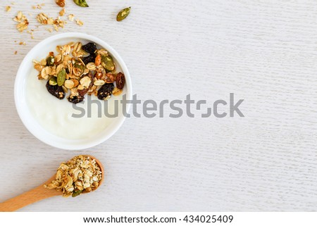 Healthy breakfast. Fresh granola, muesli in a cup. copy space.Organic oat,almond and sunflower seeds - stock photo