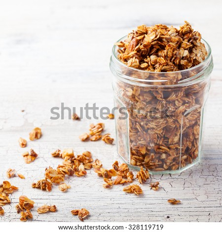 Healthy breakfast. Fresh granola, muesli in a glass jar. copy space.Organic oat,almond and sunflower seeds - stock photo