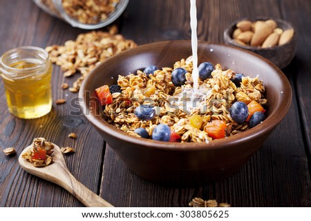 Healthy breakfast.  Fresh granola, muesli with berries, honey and pouring milk in a wooden bowl on a wooden background - stock photo