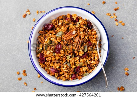 Healthy breakfast. Fresh granola, muesli with pumpkin,pecan nuts,cranberries and maple syrup in white bowl. Copy space. Top view - stock photo