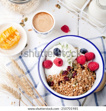 Healthy breakfast. Granola, muesli with pumpkin seeds, honey, yogurt and fresh berries in a ceramic bowl  with a cup of coffee on white background.  - stock photo