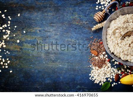 Healthy breakfast. Home made oatmeal porridge, goji berries, banana, pumpkin and chia seeds  in a metal bowl on wooden rustic background.  - stock photo