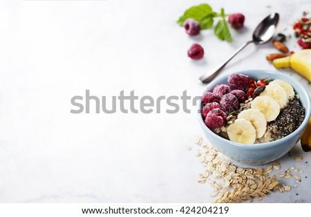 Healthy breakfast. Home made oatmeal porridge, goji berries, pumpkin and chia seeds  in a ceramic bowl on white background.  - stock photo