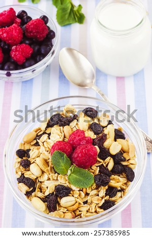 Healthy breakfast. Honey glazed oatmeal, nut and coconut chips granola in a glass bowl with yogurt and fresh berries on a textile background - stock photo