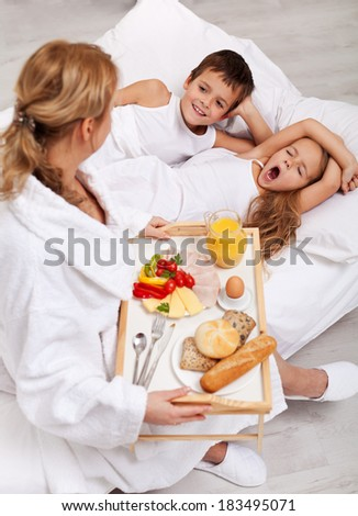 Healthy breakfast in bed for the kids - a mother caring for her offspring - stock photo