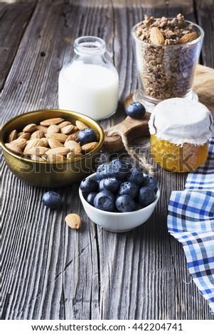 Healthy breakfast ingredients. Cereal, chocolate muesli, fresh blueberries, jar with honeycombs, rustic milk bottle on a simple plank dark background in rustic style. selective focus - stock photo
