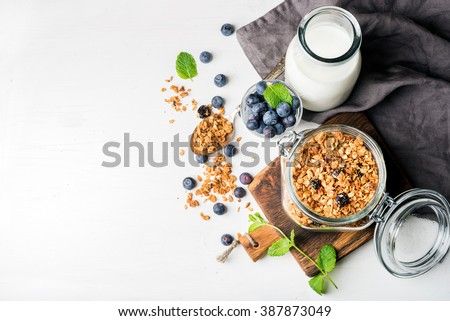 Healthy breakfast ingredients. Homemade granola in open glass jar, milk or yogurt bottle, blueberries and mint on white wooden background, top view, copy space