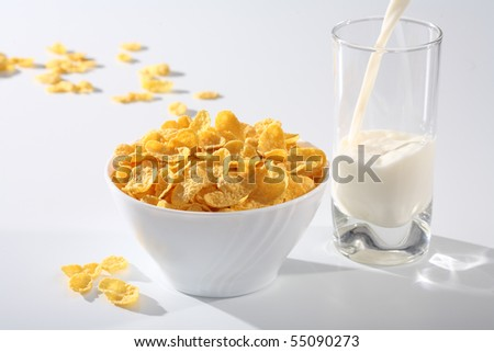 Healthy breakfast - milk with corn flakes on white - stock photo