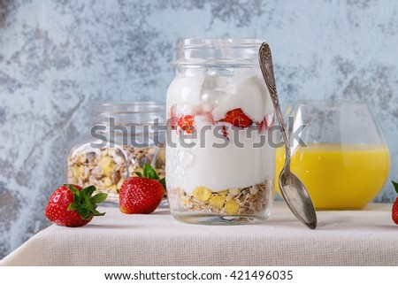 Healthy breakfast muesli, strawberries and yogurt with mango smoothie in glass mason jars. Served with fresh strawberry on white tablecloth with textured wall at background. Rustic style. - stock photo