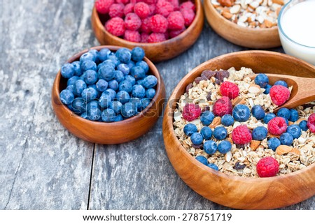 healthy breakfast muesli with berries and milk in wooden plate - stock photo
