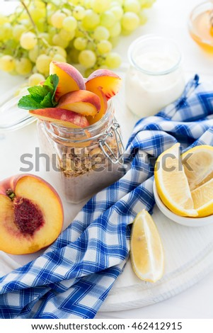 Healthy breakfast: muesli with smoothie, honey, yogurt and fresh berries in a glass jar on white wooden background