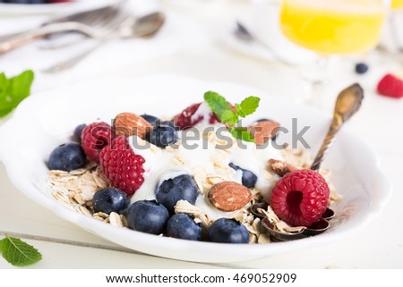 Healthy breakfast. Oat flakes with fresh berries , yogurt and honey on white table.