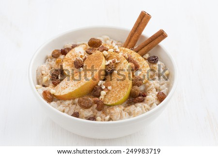healthy breakfast - oatmeal with apples, raisins and cinnamon, close-up, horizontal - stock photo