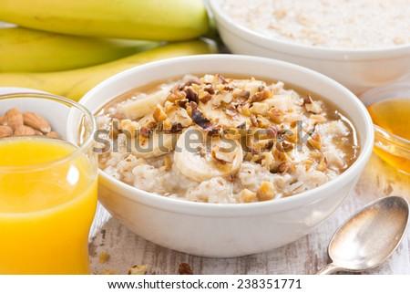 healthy breakfast - oatmeal with banana, honey and walnuts, close-up - stock photo